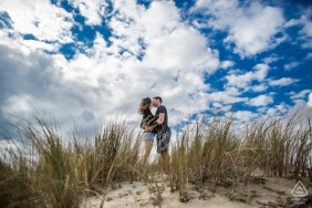 Bassin d Arcachon, France mini beach couple photography session before the wedding day with A kiss on a sand dune under blue skies with clouds