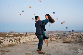 Cappadocia, Turkey micro outdoor mountain photo session before the wedding day with a playful lift as the balloons are also lifting off