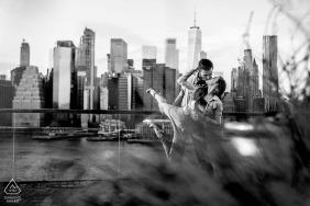 Mini-sessão de fotos de casal no Brooklyn Bridge Park, em Nova York antes do dia do casamento em um abraço de dançarinos com o horizonte da cidade atrás deles