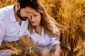French pre wed couple in the field with a warm embrace in warm tones