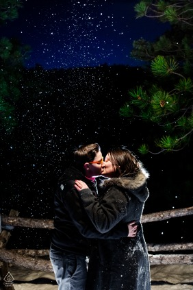 Boulder, Colorado night couple shot as they cozy up in the falling snow after dark at their winter engagement session