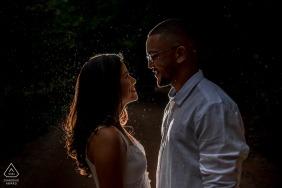 Maceió night pre wedding shoot while a light rain falls, a couple smiles against the backlight