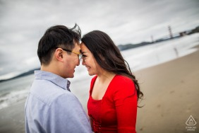 San Francisco beach couple portrait session of a sweet hearty moment by the cold ocean