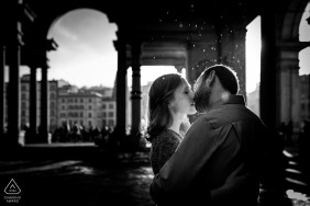 Italian pre-wed portrait at the Uffizi Gallery in Florence showing The couple is kissing into the rain and in the backlight
