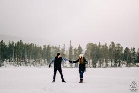 Colorado engagé séance photo d'hiver au lac Sprague dans le RMNP avec le couple dansant sur un lac gelé