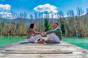 Jaen couple engagement pic session at Hotel Noguera de la Sierpe in Arroyo Frío on the wooden dock at the water, sitting and holding hands
