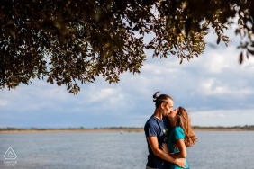 Isola di Barbana pre - wed image in Grado, Italy with a Kiss at sunset under the trees in the wind