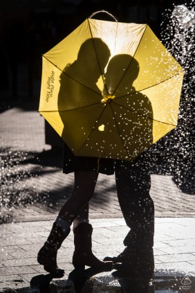 Fort Collins couple pre-wed Silhouette portrait behind umbrella with fountain in the foreground, inspired by TV show How I Met Your Mother
