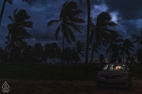Maceio couple pre-wed portrait inside a lit car at dusk below the palm trees