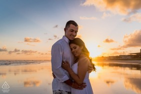 Maceio engaged couple picture session with a sunset hug at the water