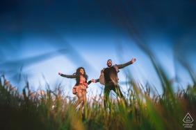 Val d'Orcia, Toscana Imagen de compromiso de bellas artes para una pareja feliz Saltando juntos en estos días de pandemia