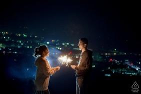 Nanning Fine Art Engagement Session de nuit avec vue sur les lumières de la ville avec un couple tenant des feux