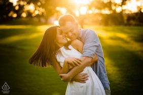 Perth Fine Art Engagement Image showing A beautiful hug on the green grass with warm sunlight