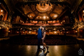 Toronto Artful Engagement Picture at a theater as the couple stand on the stage in formal clothes