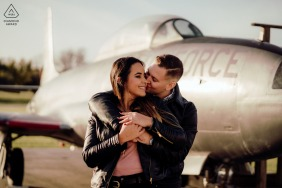 Bolingbrook Fine Art Pre Wedding Portrait at the Illinois Aviation Museum with a Couple embracing in front of fighter jet