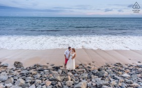 Maceió Fine Art Engagement Image showing the couple is standing on rocks on the beach