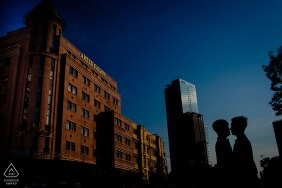 Ho Chi Minh Fine Art Pre Wedding Portrait with silhouettes and towering city buildings under a dark blue sky