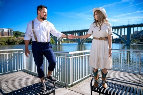 Volunteer Landing Park, Knoxville on-location portrait e-shoot - the couple holds hands at the park with the Henley Street Bridge and the Tennessee River as their background