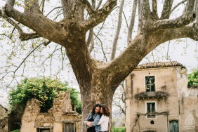 Naples on-location portrait e-shoot of couple holding one another standing with a large tree
