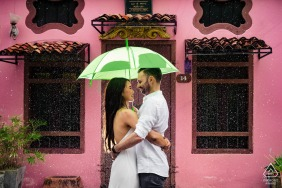 Phuket portrait e-session with bright pink building and an umbrella to escape the rain