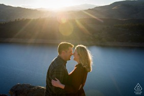 Horsetooth Reservoir, Fort Collins environmental engagement e-session - a couple shares a laugh under the setting sun high above a reservoir