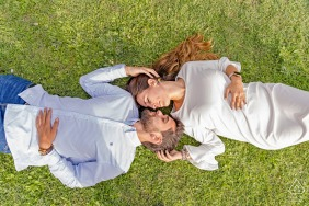 Cazorla, Jaén on-location portrait e-shoot overhead with couple in white lying on backs on the grass
