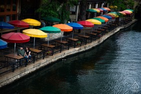 Riverwalk/San Antonio, TX portrait e-session with a couple sitting at a table surrounded by colorful sun umbrellas