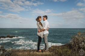 Saint Cast, France e-session portrait avec le couple face à face debout au-dessus de l'océan sur les falaises