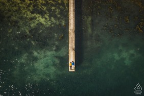 Golf du Morbihan, France drone on-location portrait e-shoot of the engaged couple lying down on a wood dock at the water