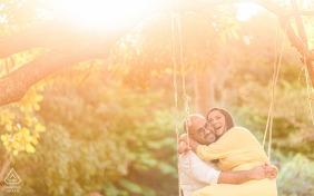 Sesión electrónica de retrato en Maceió, Alagoas con un hombre y una mujer en una casa de campo, sentados en un columpio y sonriendo