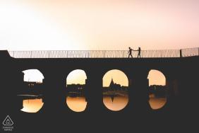 Sesja portretów zaręczynowych prawdziwej miłości w Syrakuzach pokazująca parę przechodzącą przez most podczas zachodu słońca na wiosnę na Sycylii
