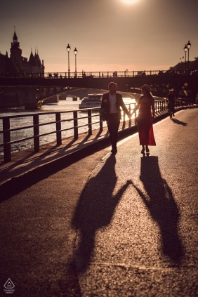 True Love Pre-Wedding Portrait Session at the River Seine in Paris illustrating a couple walking away from the sunset throwing large shadows