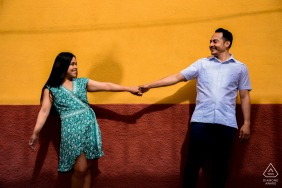 True Love Engagement Posed Portrait at the Calle Terraplen in San Miguel de Allende capturing the striking colors of the walls with a fun pose