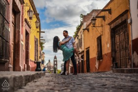 True Love pre wedding Photoshoot at the Calle Recreo in San Miguel de Allende of a couple with The intention to capture the church in the background with a fun dancing pose