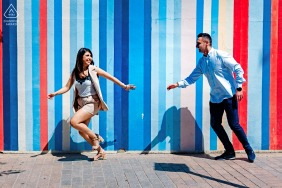 True Love Engagement Portrait Session in Cordoba, Spain displaying a couple running in the urban sunshine near a vertical painted striped wall