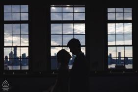 True Love Pre-Wedding Portrait Session in Manhattan, die ein Paar in einer Wohnung mit Blick auf die Skyline der Stadt aus den Fenstern zeigt