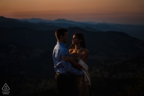 True Love pre wedding Photoshoot at Lost Gulch Overlook in Boulder, CO of a couple embracing during sunset, in front of a distant mountain view