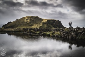True Love Pre-Wedding Portrait Session in Iceland illustrating a couple reflected in the water from the cliffs below the clouds
