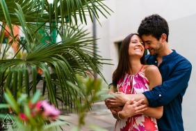 True Love Engagement Portrait Session in Muggia, Trieste displaying a couple embracing before a white building with palms