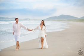 Buzio couple e-shoot in Rio de Janeiro while walking hand in hand on the beach sands by the sea