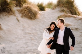 Montpellier, FR couple e-shoot in formal attire walking on the sand dunes in the sunshine