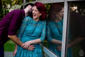 Bucharest bride and groom to be, posturing for an engagement image against a window showing their laughing reflections