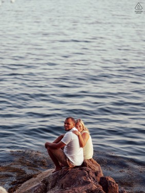 Rockport, ME bride and groom to be, sitting for a pre-wedding engagement session on Rocks by the Water