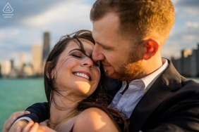 Chicago bride and groom to be, hugging for an engagement image at North Avenue Beach while embracing by the lakefront