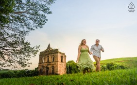 Alagoas bride and groom to be, posing for a São Luiz do Quietude pre-wedding engagement photo shoot of the couple holding hands and run together on a green lawn. In the background, ruins of a farm