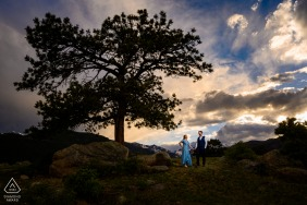 On location RMNP engagement portrait shootas a couple takes a stroll through a meadow
