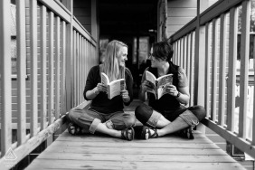 Hudson, MA environmental couple pre wedding image sessionwhile reading books and seated on a wooden walkway