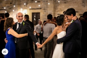 The bride's dad holds his daughter's hand during the first dance with her husband at Masseria San Lorenzo, Lecce