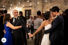 Il padre della sposa tiene la mano di sua figlia durante il primo ballo con suo marito alla Masseria San Lorenzo, Lecce