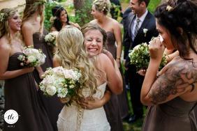 Rodeada de miembros de la fiesta de bodas, una dama de honor cierra los ojos mientras abraza a la novia momentos después de la ceremonia de la boda | Imagen de la boda de South Lake Tahoe